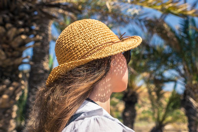 Back view on the Woman in the straw hat walking in the palm forest and shows a finger on the trees. Seychelles islands. stock image