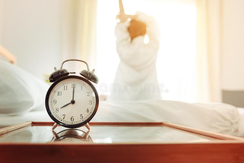 Back view of woman stretching in morning after waking up on bed near window with alarm clock. Holiday and Relax concept. Lazy day. And Working day concept royalty free stock photography