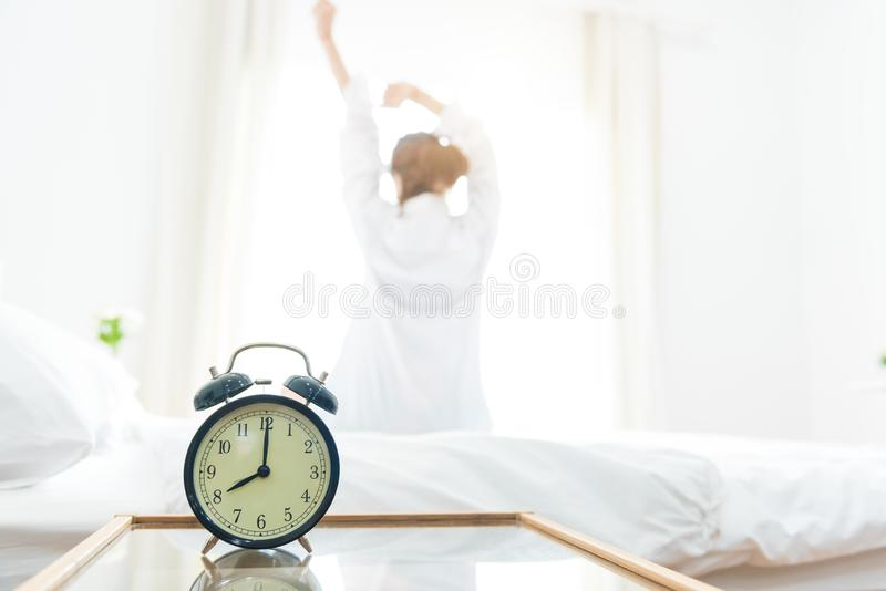 Back view of woman stretching in morning after waking up on bed near window with alarm clock. Holiday and Relax concept. Lazy day. And Working day concept stock photos