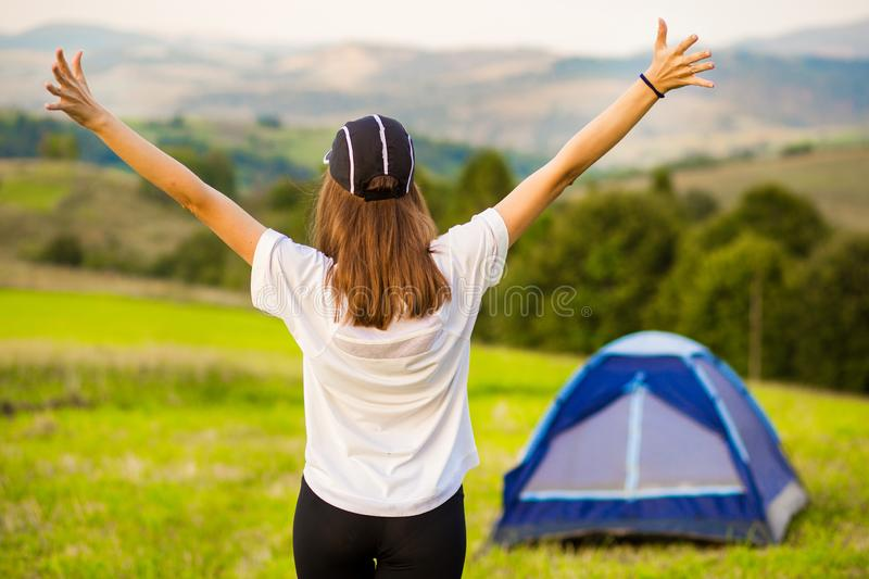 Back view of woman successful hiking climbing in mountains, motivation. Hiker with arms up outstretched stock photography