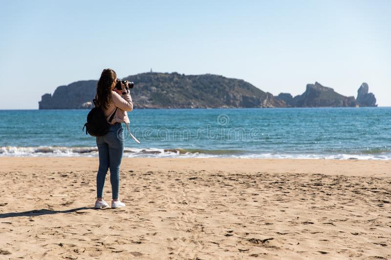 Back view of woman taking pictures with DSLR camera of islands from the beach - Medes Islands stock photography