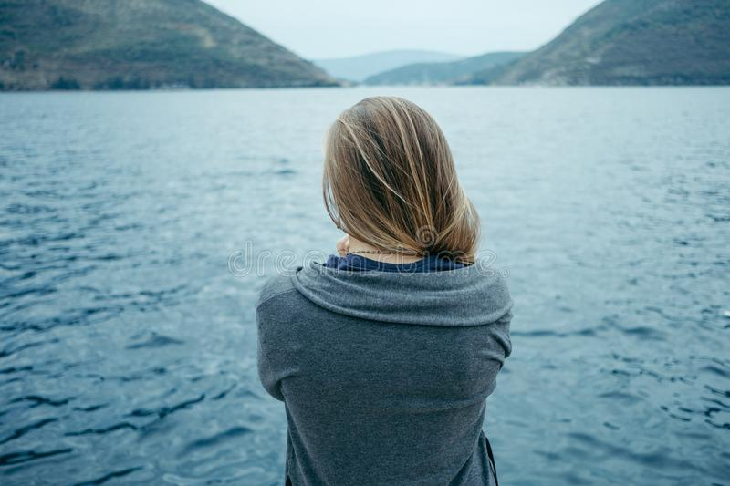 Back view of woman thinking alone and watching the sea with the royalty free stock photography