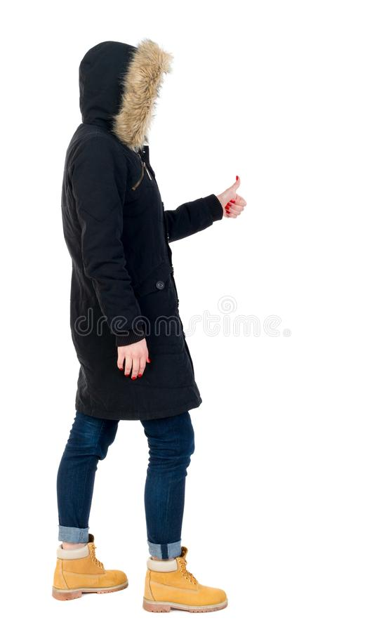 Back view of woman thumbs up. Girl in warm winter jacket is black with cancer and shows thumb up stock images