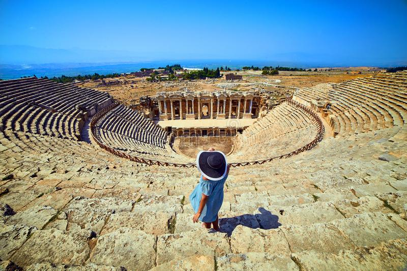 Back view of woman traveler in hat looking at amazing Amphitheater ruins in ancient Hierapolis, Pamukkale, Turkey. Grand panorama stock photography