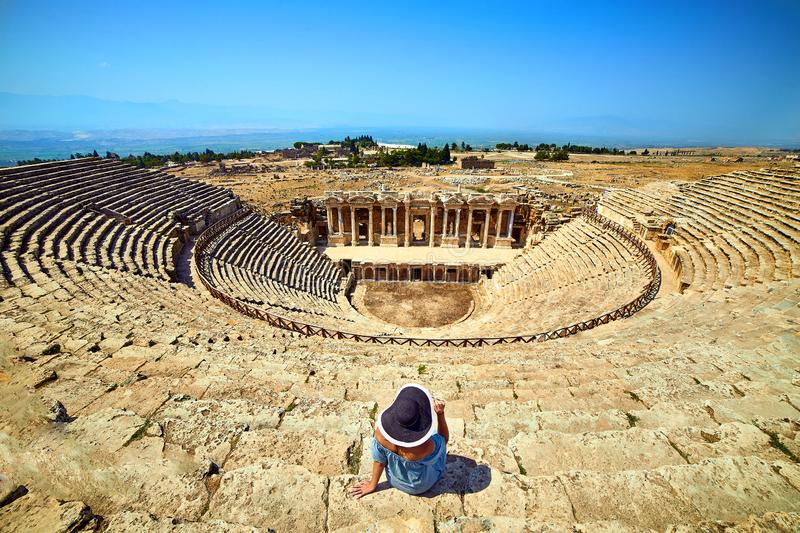 Back view of woman traveler in hat looking at amazing Amphitheater ruins in ancient Hierapolis, Pamukkale, Turkey. Grand panorama royalty free stock photography