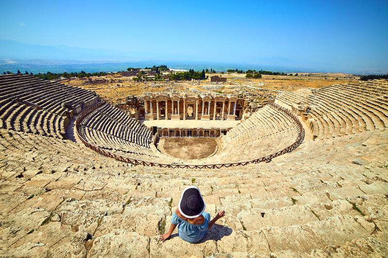 Back view of woman traveler in hat looking at amazing Amphitheater ruins in ancient Hierapolis, Pamukkale, Turkey. Grand panorama royalty free stock photo