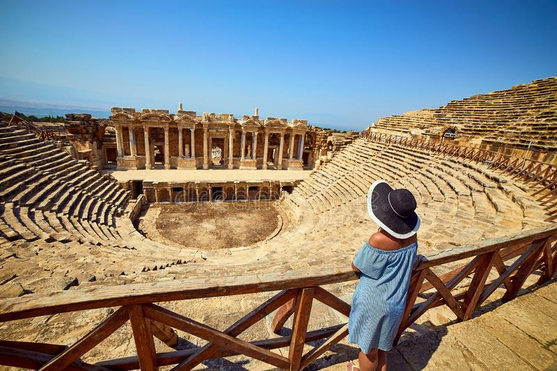 Back view of woman traveler in hat looking at amazing Amphitheater ruins in ancient Hierapolis, Pamukkale, Turkey. Grand panorama stock images