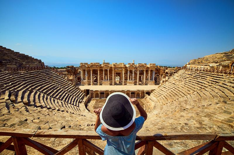 Back view of woman traveler in hat looking at amazing Amphitheater ruins in ancient Hierapolis, Pamukkale, Turkey. Grand panorama stock photo