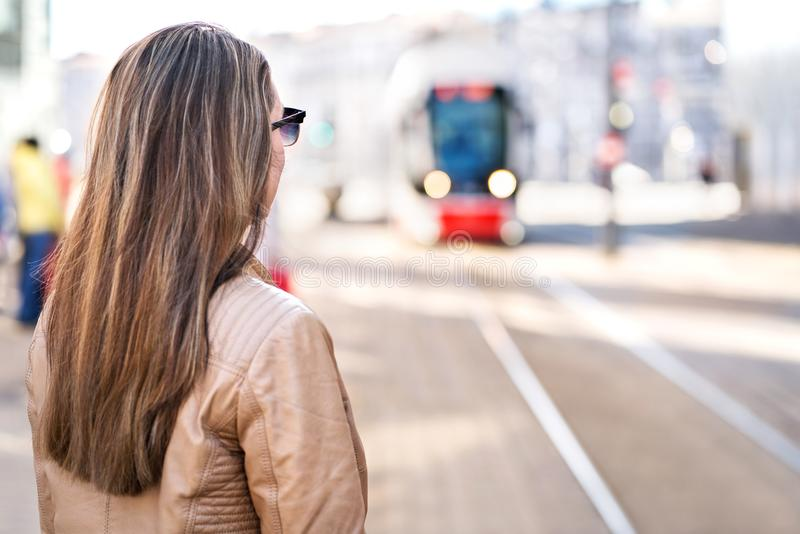 Back view of woman waiting for tram in stop royalty free stock images