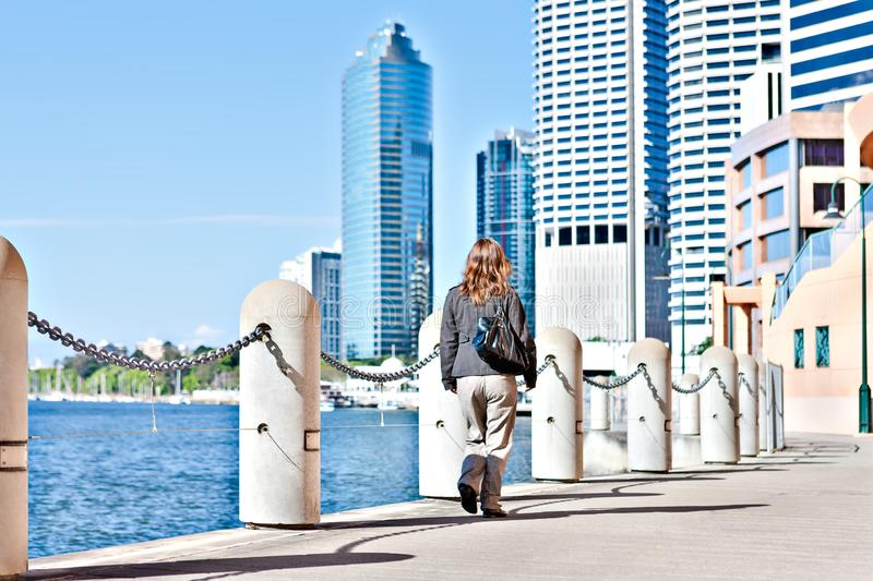 Back view of a woman walking along the footpath royalty free stock photography
