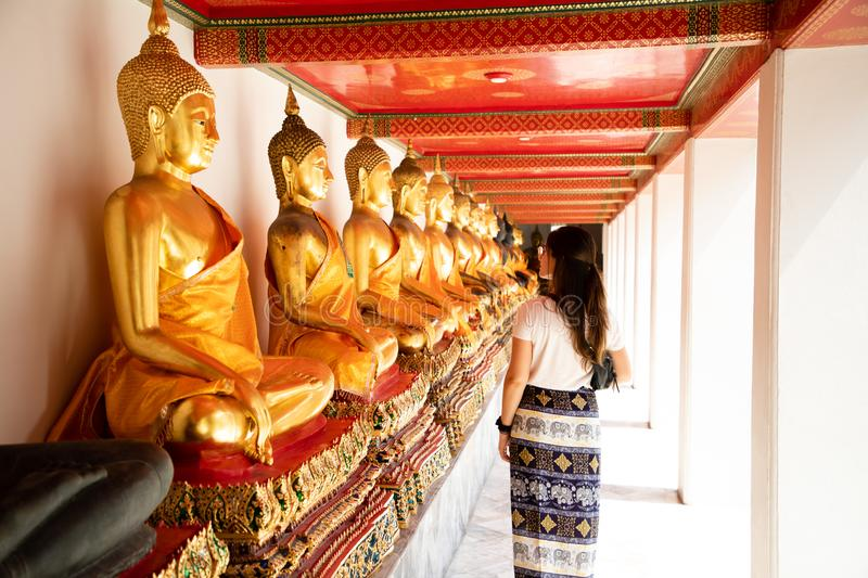 Back view of a woman walking side to aligned golden Buddha Statues at the Emerald temple in Bangkok stock photography