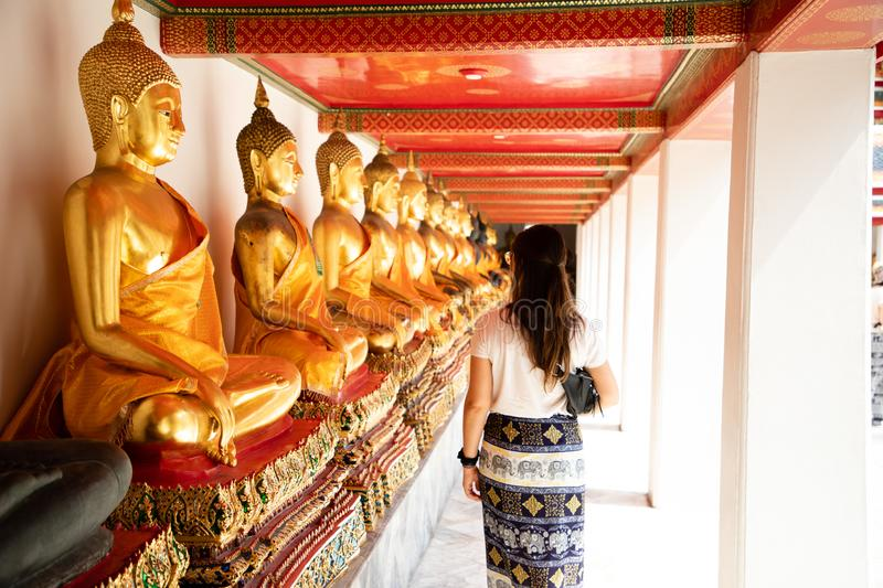 Back view of a woman walking side to aligned golden Buddha Statues at the Emerald temple in Bangkok royalty free stock photos
