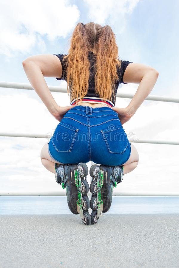 Back view woman wearing roller skates and shorts stock photo
