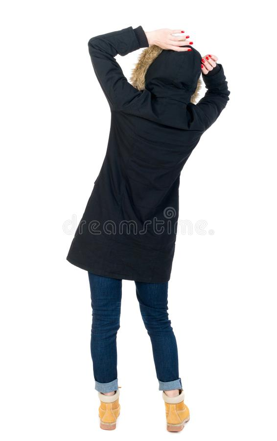 Back view woman in winter jacket Balances waving his arms. Standing young girl in parka. girl in warm winter jacket black fright clutched her head royalty free stock images