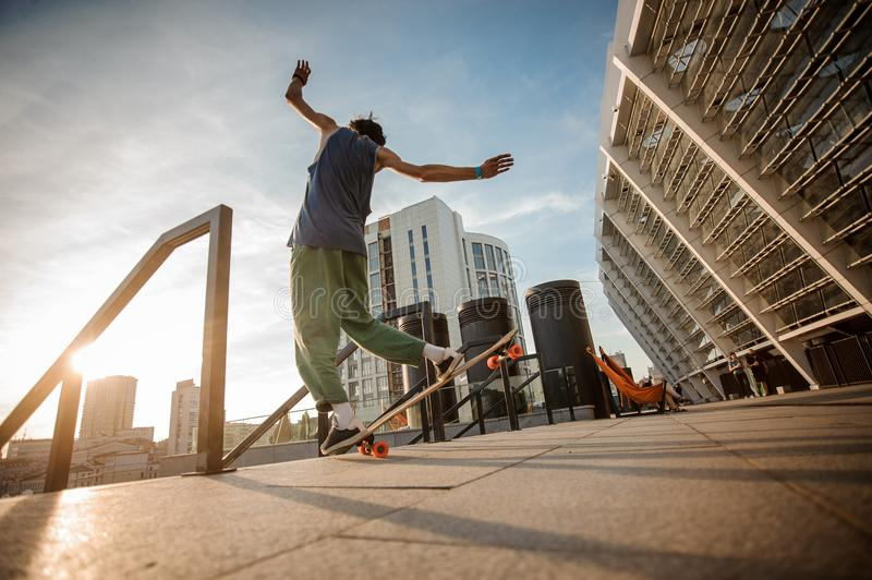 Back view of young active man jumping on skateboard against the stock image