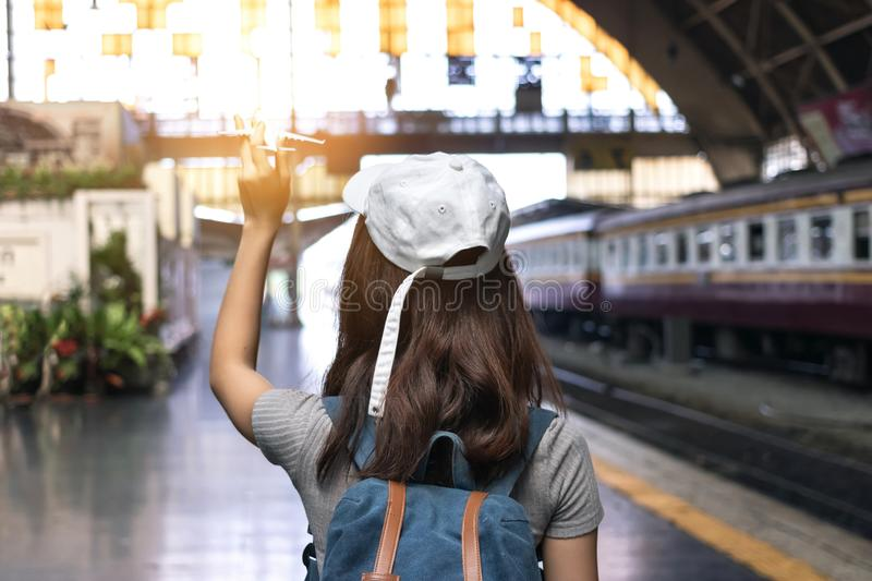Back view of young Asian tourist girl holding model airplane at train station. Travel lifestyle concept royalty free stock photo