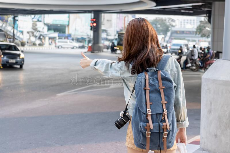 Back view of young Asian travel girl hitchhiking on the road in city. Life is a journey concept stock photography