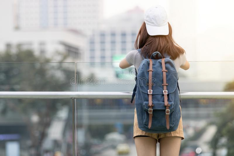 Back view of young Asian woman tourist looking at the sights of city. Travel and vacation concept royalty free stock photos