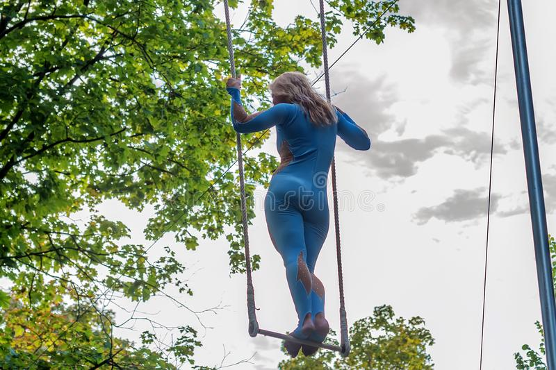 Back view young attractive female trapeze artist. Close up back view of a blond woman in costume standing on rapeze outdoors stock photos