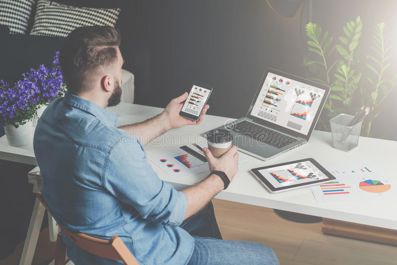 Back view.Young bearded businessman in shirt sits in office at table and uses smartphone with charts,diagrams and graphs. On screen and drinks coffee.On desk is royalty free stock photos