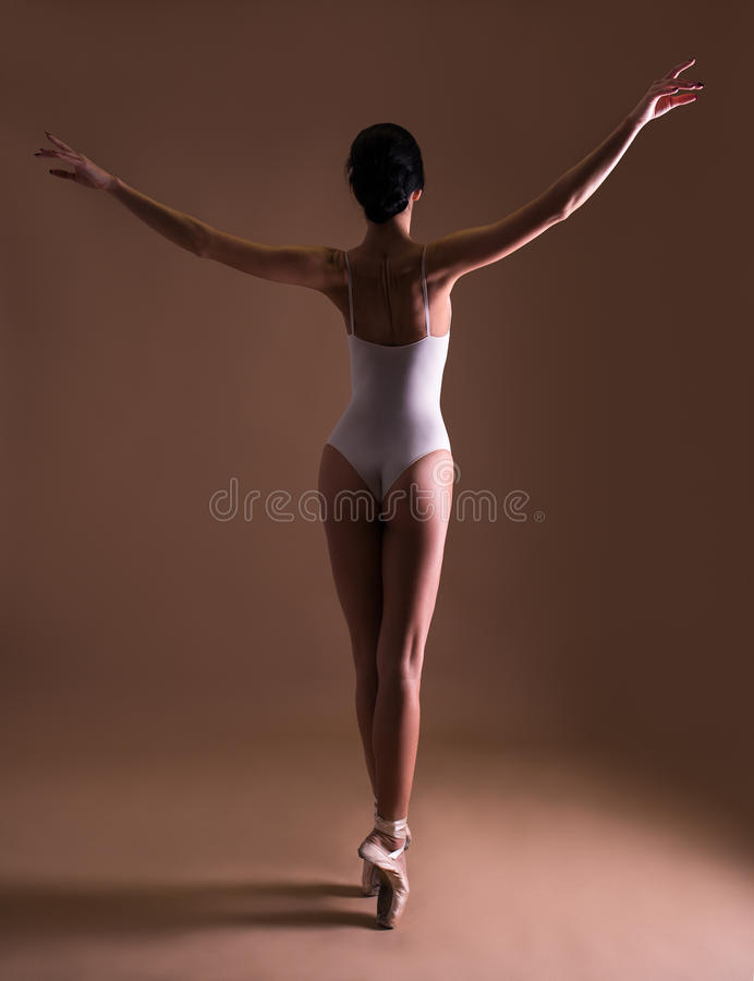 Back view of young beautiful woman ballet dancer posing on toes. Over beige background stock images