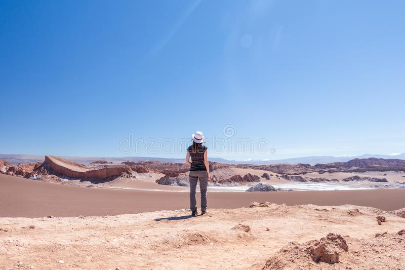 Back view of young blond casual woman in hat explore stunning landscape of Moon Valley in Atacama Desert, Chile. Back view of active woman, female carefree solo stock photography