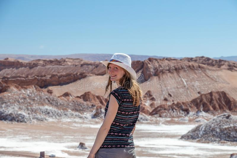 Back view of young blond casual woman in hat explore stunning landscape of Moon Valley in Atacama Desert, Chile. Back view of active woman, female carefree solo royalty free stock photo