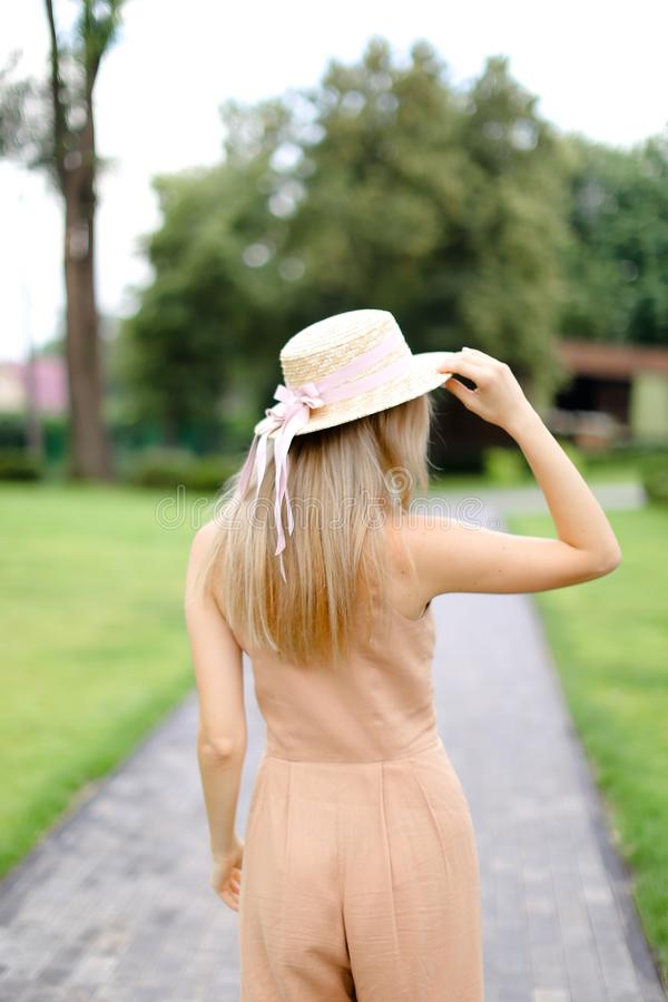 Back view of young blonde female person in body color overalls and hat. royalty free stock photos