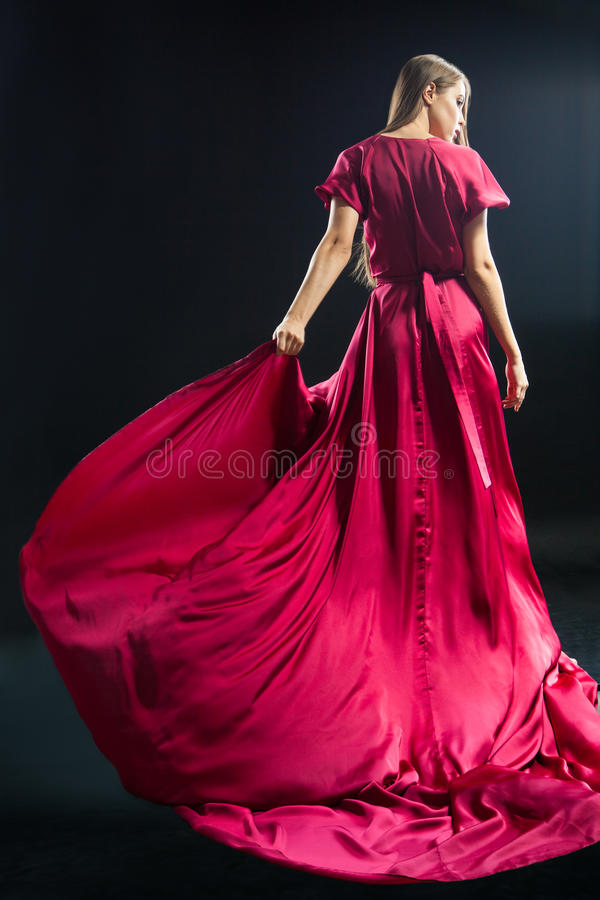 Back view of young blonde woman in bright pink dress. Portrait of blonde girl looking away in bright elegant pink dress against of black background royalty free stock images