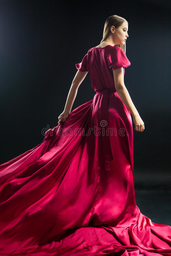 Back view of young blonde woman in bright pink dress stock photo