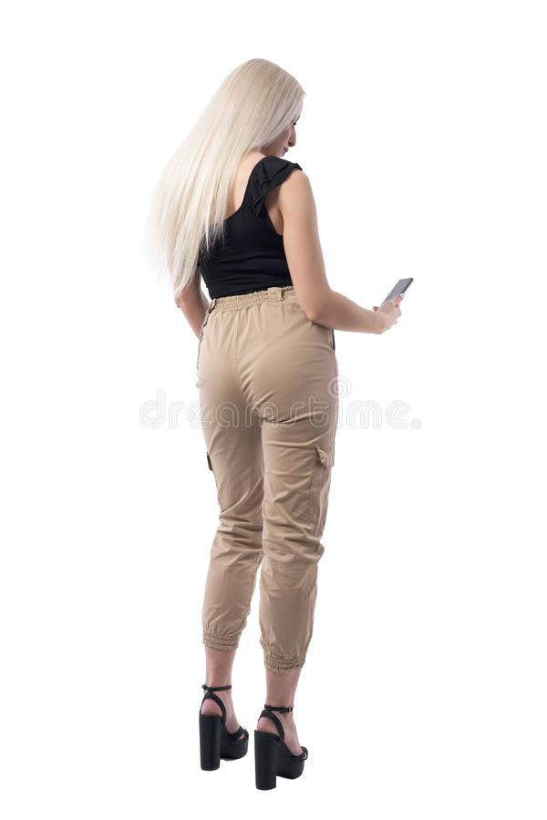 Back view of young blonde woman in fashionable clothes using mobile phone. Full body isolated on white background stock photo