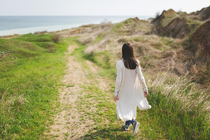 Back view Young brunette woman in light casual clothes walking along path in sunny weather in field near water on green. Background. Beautiful landscape royalty free stock images