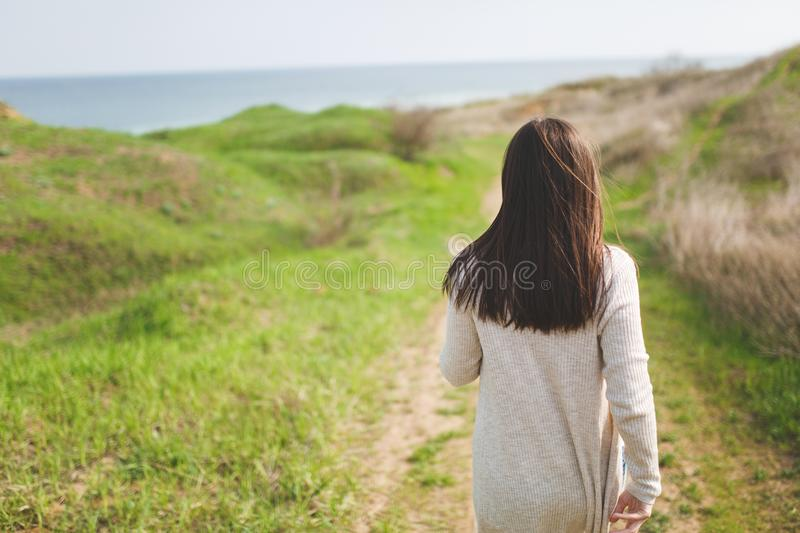 Back view Young brunette woman in light casual clothes walking along path in sunny weather in field near water on green. Background. Beautiful landscape royalty free stock image