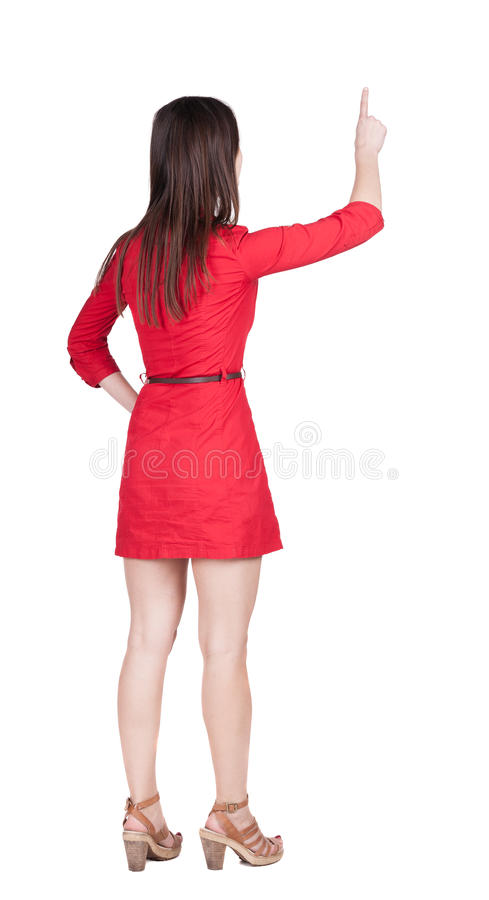 Back view of young brunette woman pointing at wall. stock image