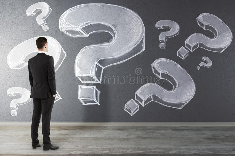Confusion concept. Back view of young businessman in interior looking at wall with drawn question marks. Confusion concept stock image