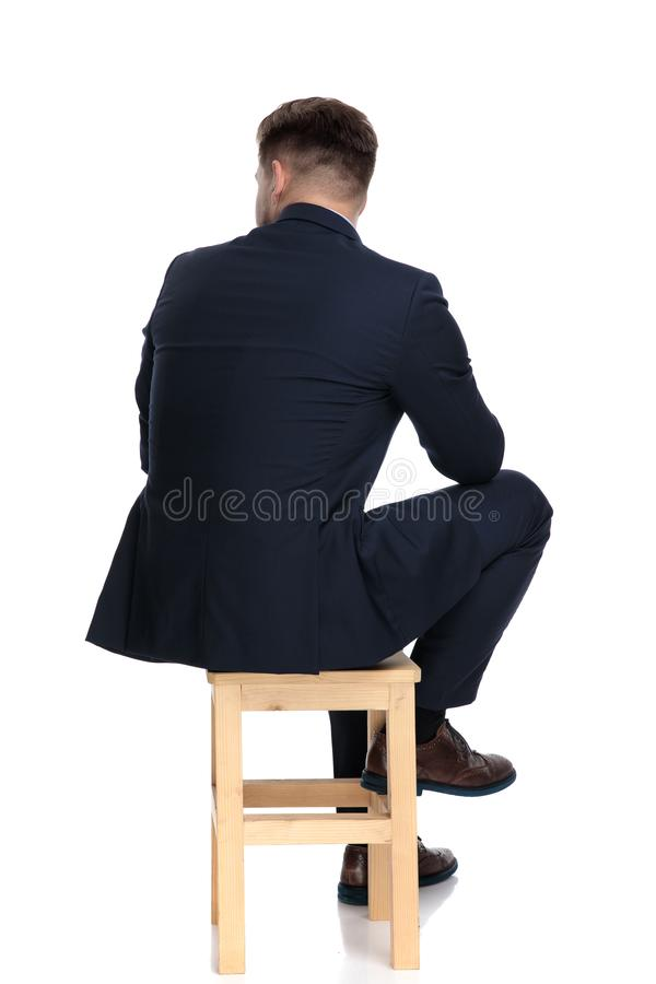 Back view of young businessman sitting on wooden chair. Back view of young businessman looking to side and thinking, sitting isolated on white background in royalty free stock image