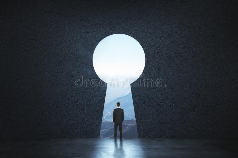 Dream, success, opportunity and innovation concept. Back view of young businessman standing against keyhole door. Dream, success, opportunity and innovation royalty free stock images