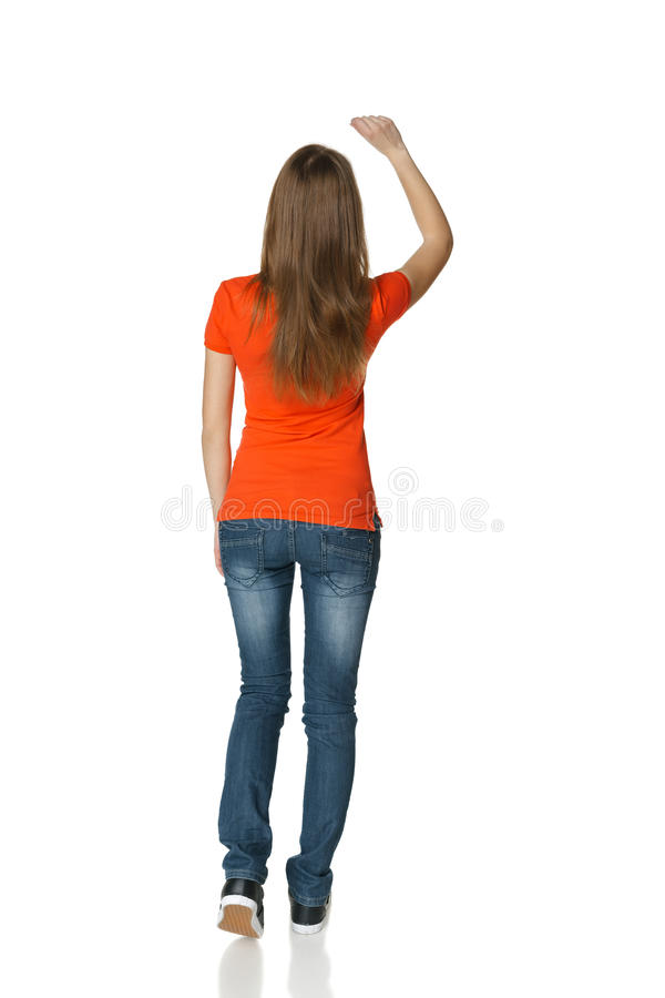 full space back view of young casual female in full length writing on the