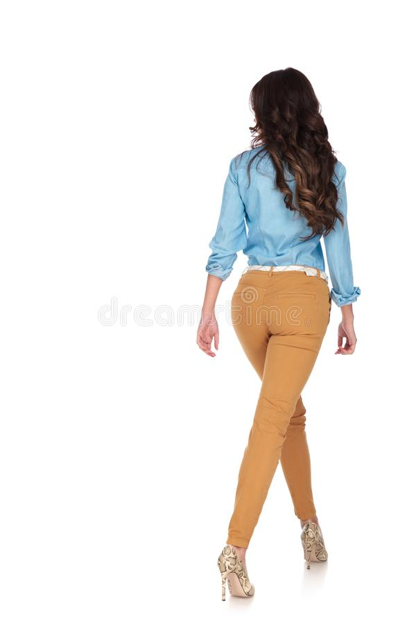 Back view of a young casual woman walking royalty free stock photo