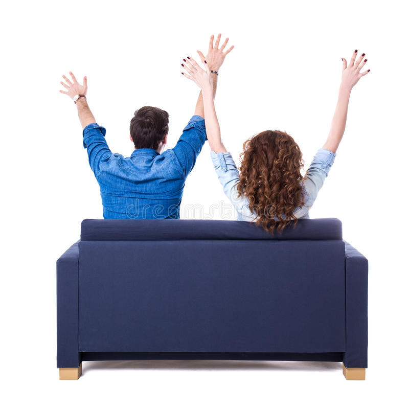 Back view of young cheerful couple sitting on sofa isolated on w royalty free stock image