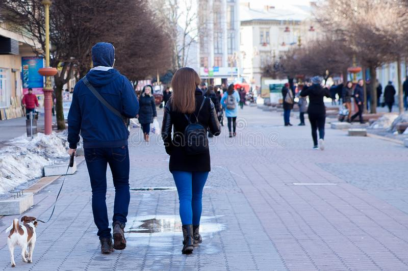Back view of a young couple walking their dog on the city street stock image