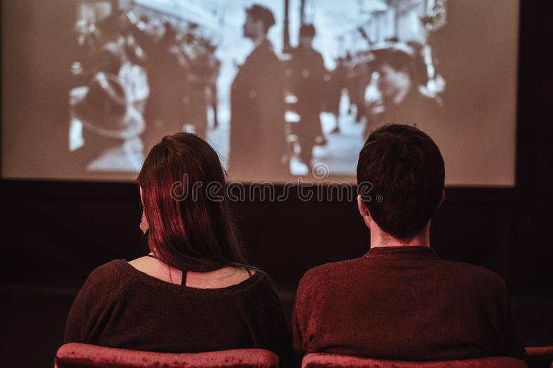 Back view of a young couple watching a retro movie in the cinema on a date stock photography