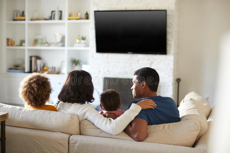 Back view of young family sitting on the sofa and watching TV together in their living room, close up stock photography