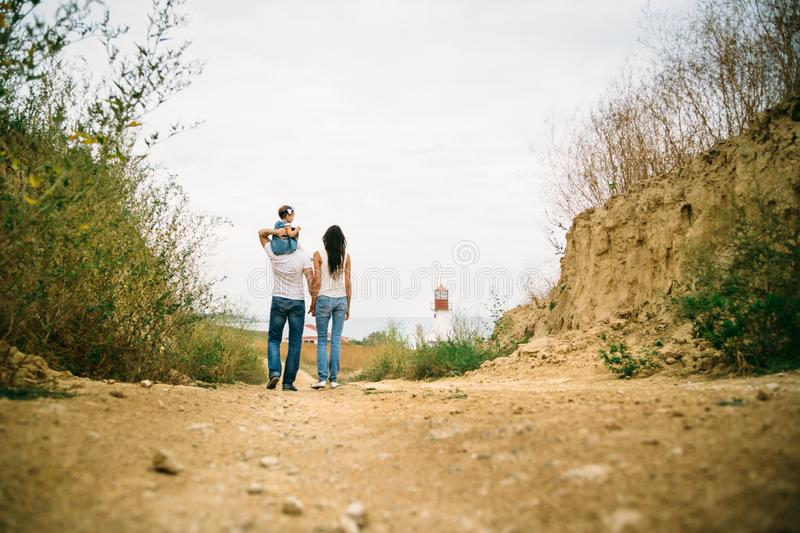 Back view of young family with a small kid walking to the white lighthouse, outdoors background royalty free stock photo
