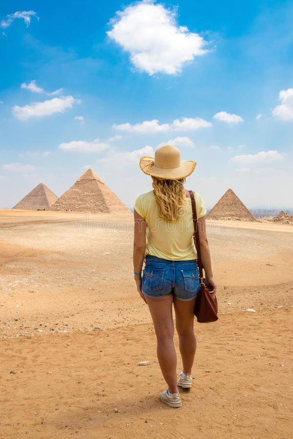 Back view of the young female with beautiful blond hairs. Back view portrait of a single woman watching the Great Pyramids of Giza stock photos