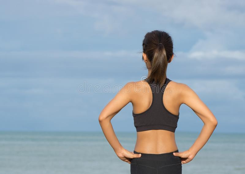 Back view of young fitness woman running on the on the beach in the morning, People and sport concept stock photo