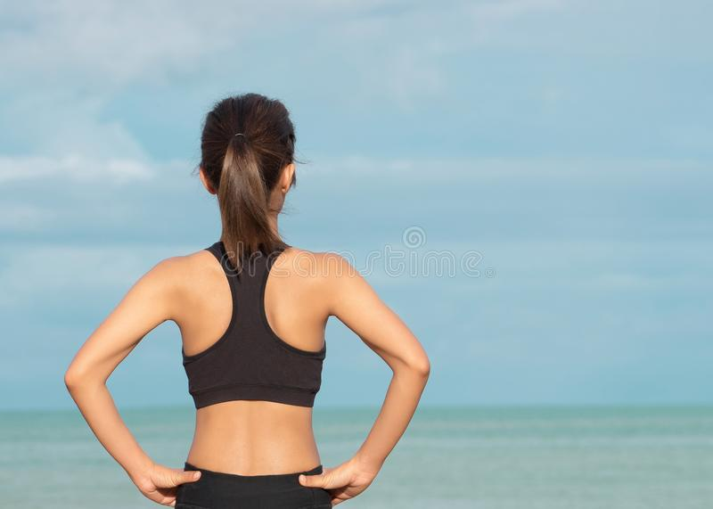 Back view of young fitness woman running on the on the beach in the morning, People and sport concept royalty free stock image
