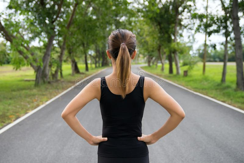 Back view of young fitness woman running on the road in the morning, People and sport concept, Selective focus stock photos