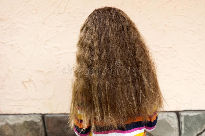 Back view of young girl head with long blond fair loose curly hair outdoors on sunny summer white stucco wall copy space royalty free stock photo