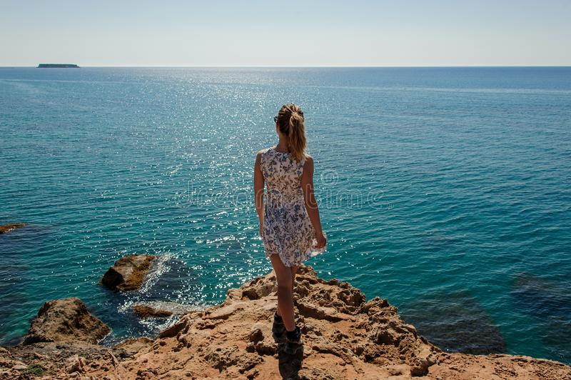 Back view young girl standing on the rock in dress royalty free stock photography